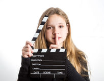 Teenage girl with clapperboard. Teenage girl in black clothes, blonde with long hair is holding clapperboard, on white background Stock Images