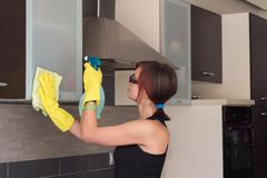 Teenage girl cleaning kitchen cabinet Stock Image