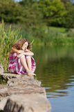 Teenage Girl With Closed Eyes Sitting On Rock. While looking away by lake stock images