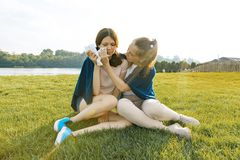 Teenage girl comforts her crying, upset, sad friend. The girls are sitting on the green grass in the park royalty free stock image