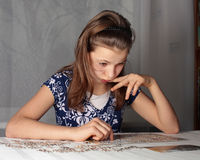 Teenage girl concentrates on puzzle. Teenage girl 12-13 years old doing puzzle on table Stock Image