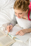 Teenage girl concentrating on studying in bed Stock Photo