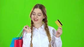 Teenage girl with a credit card and packages in her hands . Green screen stock video