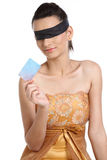 Teenage girl with credit card tied band to eyes. Teenage girl  with black band holding blank credit card Royalty Free Stock Image