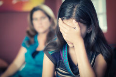 Teenage girl cries with her mother on the background. Teenager problems - Teenage girl cries while her mother looks at her on the background Stock Image
