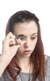 Teenage Girl Curling Eyelashes with Eyelash Curler Stock Images