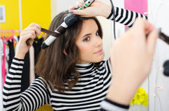 Teenage girl curling long hair with curler in front of mirror Stock Photos
