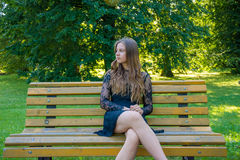 Teenage girl on date waiting sitting on bench in park. Young teenage girl in black dress waiting for a date watching out her boyfriend with nervous feelings royalty free stock images