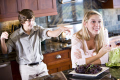Teenage girl daydreaming in kitchen brother poking Stock Images