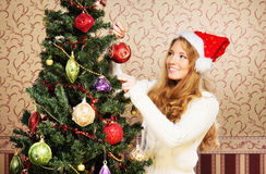 A teenage girl decorating the Christmas tree Royalty Free Stock Photography