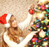 A teenage girl decorating the Christmas tree Stock Photos
