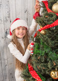 Teenage girl decorating New Year tree at home Stock Photos