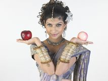 Teenage  girl with designer sari holding apples Stock Photo