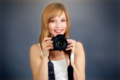 Teenage girl with digital camera. On gray background Royalty Free Stock Photo