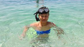 Teenage girl in diving mask standing in shallow water of blue sea. Teenager in diving mask and snorkel standing in clear water of blue sea and smiling at camera stock video