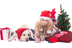 Teenage girl with dog in santa hat and christmas tree isolated o Royalty Free Stock Photos
