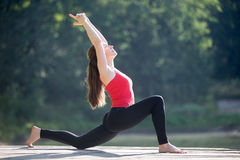 Teenage girl doing crescent lunge pose. Fit young woman working out outdoors in park on summer day, doing crescent lunge pose (anjaneyasana), Horse posture ( royalty free stock photography