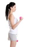 Teenage girl doing exercise using dumbbells. royalty free stock photography