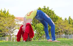 A teenage girl  is doing flexibility exercise. A teenage girl is doing flexibility on the lawn in a park on a sunny day Stock Photo