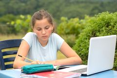 Teenage girl doing her homework in the garden Royalty Free Stock Photography