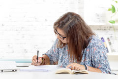 A teenage girl doing her homework Royalty Free Stock Photo
