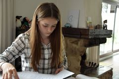 Teenage girl doing her maths homework royalty free stock images