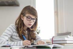 Teenage girl doing homework at table Stock Photo