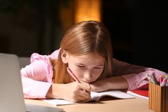 Teenage girl doing homework at table. In evening Royalty Free Stock Photos
