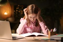 Teenage girl doing homework at table. In evening Stock Photography