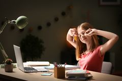 Teenage girl doing homework at table. In evening Stock Photos