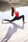 Teenage girl doing lunge posture. Fit young woman wearing red tank top and black sporty leggings working out outdoors on wooden pontoon on the lake, doing low royalty free stock photo
