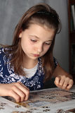 Teenage girl doing puzzle. Teenage girl 12-13 years old doing puzzle on table Stock Images