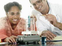 Teenage girl (15-17) doing science experiment at desk in classroom, teacher assisting, smiling Royalty Free Stock Photos
