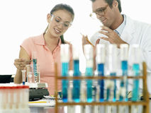 Teenage girl (15-17) doing science experiment at desk in classroom, teacher assisting, smiling Royalty Free Stock Photography