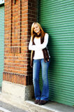 Teenage girl in doorway. A view of a pretty teenage girl standing casually in a doorway or garage entrance on a city street royalty free stock images