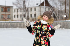 A teenage girl in a down jacket in winter, ice skating, Stock Image