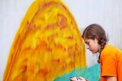 Teenage girl draw the graffiti. Teenage girl draw a graffiti on a wall Stock Photo