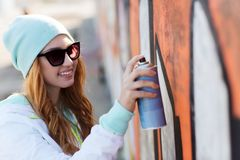 Teenage girl drawing graffiti with spray paint Stock Photography