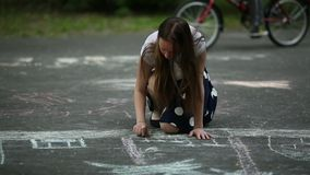 Teenage girl draws with chalk on the pavement in the street. stock video
