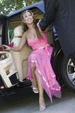 Teenage girl in dress being helped out of limo Royalty Free Stock Images