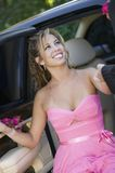 Teenage girl in dress being helped out of limo Royalty Free Stock Photography