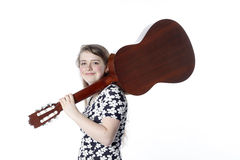 Teenage girl in dress holds guitar on shoulder in studio Royalty Free Stock Photos