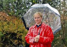 Teenage girl dressed for rain. Teenage girl dessed for rainy day in bright red raincoat Royalty Free Stock Photos