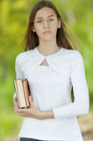 Teenage girl dressed in white with books Stock Photos