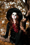 Teenage girl dressed in witch costume sitting on the tree Stock Photography