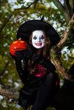 Teenage girl dressed in witch costume sitting on the tree Stock Images