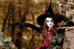 Teenage girl dressed in witch costume sitting on the tree Royalty Free Stock Image