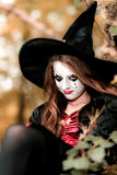 Teenage girl dressed in witch costume sitting on the tree Stock Photo