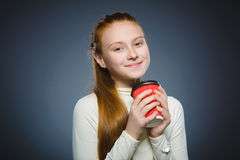 Teenage girl drink red cup of coffee isolated on gray background stock photos