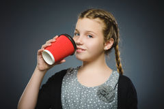 Teenage girl drink red cup of coffee isolated on gray background Royalty Free Stock Photo